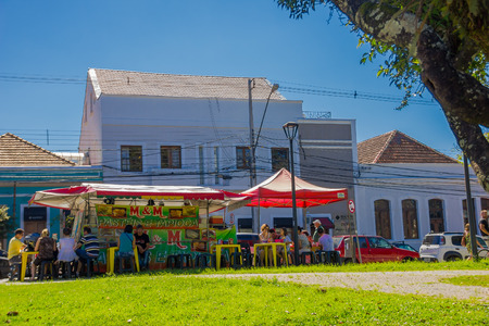 CURITIBA ,BRAZIL - MAY 12, 2016: some people eating outside next to a little food stand that offers some traditional brazilian food. Editorial