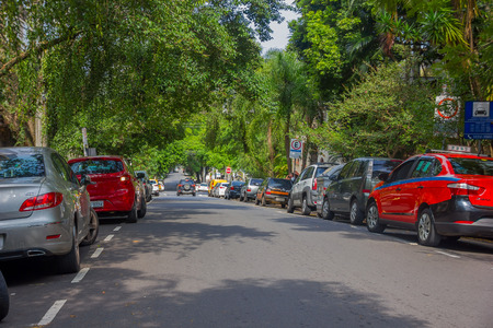 sidewalks: PORTO ALEGRE, BRAZIL - MAY 06, 2016: cars parked on the side of the street, nice big trees in the sidewalk