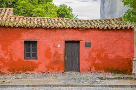 casa colonial: Colonia del Sacramento, URUGUAY - mayo 04, 2016: pequeña casa roja con un cartel al lado de la puerta diciendo que el año en que la casa fue construida.