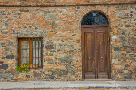 colonia del sacramento: COLONIA DEL SACRAMENTO, URUGUAY - MAY 04, 2016: ancient house builded with bricks and stones, the door and the window are made of wood.
