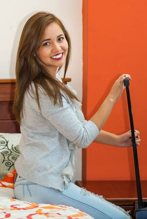 guest: Young pretty hispanic woman wearing casual clothes sitting on bed holding onto suitcase handle, hostel guest concept. Stock Photo