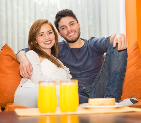 departing: Young charming couple seated and embracing in orange sofa smiling to camera, hostel environment. Stock Photo