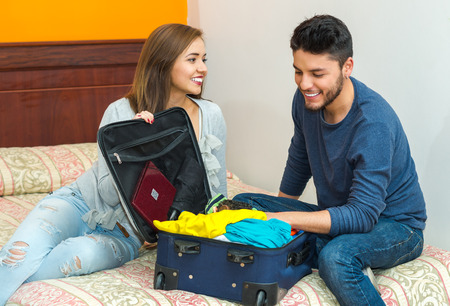 hostel: Young charming hispanic couple wearing casual clothes sitting on bed packing into suitcase together, hostel guest concept.