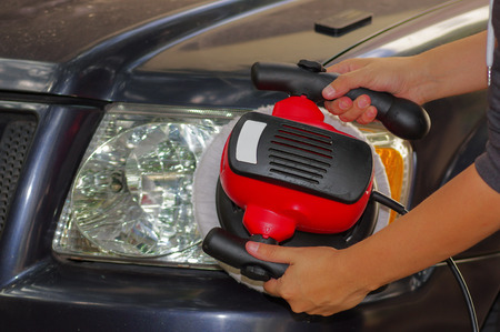 polisher: hand with a polisher cleaning the car headlights.