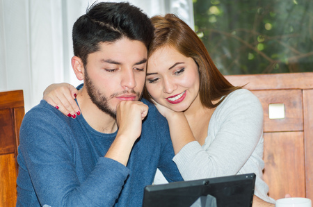departing: Young charming couple seated by table watching tablet screen while embracing, bot happy and smiling, hostel concept. Stock Photo