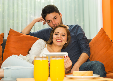 guest house: Young charming couple seated and embracing watching tablet screen in orange sofa smiling to camera, hostel environment. Stock Photo