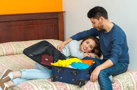 packing suitcase: Young charming hispanic couple wearing casual clothes sitting on bed packing into suitcase together, hostel guest concept.