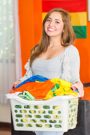 Young pretty woman wearing casual clothes holding laundry basket and smiling to camera, orange wall with flags in background, hostel guest concept.