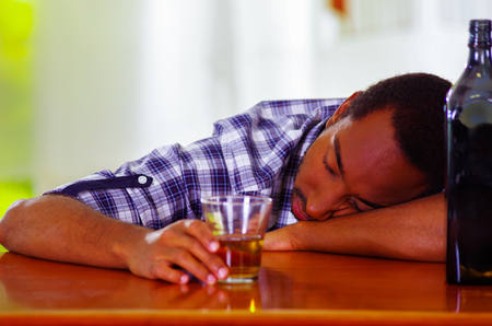 over the counter: Handsome man wearing white blue shirt sitting by bar counter lying over desk drunk sleeping, alcoholic concept.