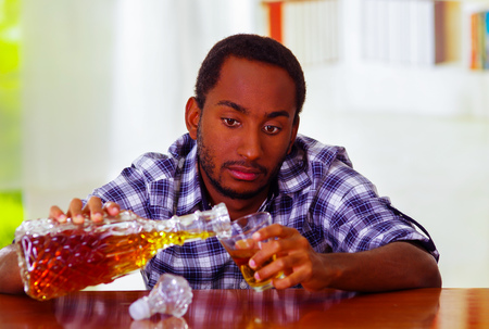 over the counter: Handsome man wearing white blue shirt sitting by bar counter lying over desk pouring drink from decanter into glass, drunk depressed facial expression, alcoholic concept.