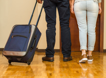 Legs of couple wearing casual pants walking towards door pulling blue suitcase, hostel guest concept.
