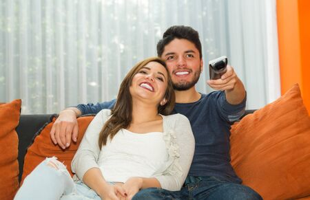 departing: Young charming couple seated in orange sofa embracing and watching television, him pointing remote control towards camera, hostel environment. Stock Photo