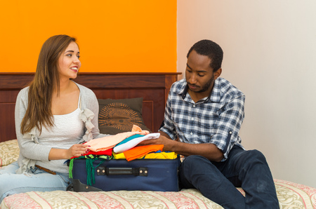 hostel: Charming young couple sitting on bed interacting happily while packing suitcase with clothes, hostel guest concept.