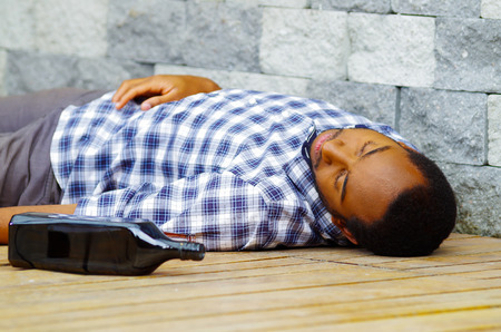 Passed out: Man wearing casual clothes lying drunk passed out on wooden surface next to grey brick wall, empty bottle beside him.