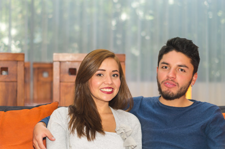 guest house: Young charming couple seated and embracing in orange sofa smiling to camera, hostel environment. Stock Photo
