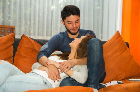 hostel: Young charming couple seated in orange sofa embracing and staring into each others eyes, hostel environment.