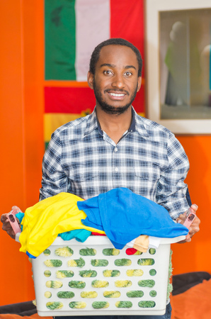 Young handsome man wearing casual clothes holding laundry basket and smiling to camera, orange wall with flags in background, hostel guest concept. Stock Photo