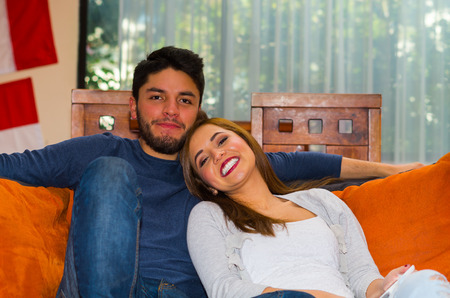 hostel: Young charming couple seated and embracing in orange sofa smiling to camera, hostel environment. Stock Photo