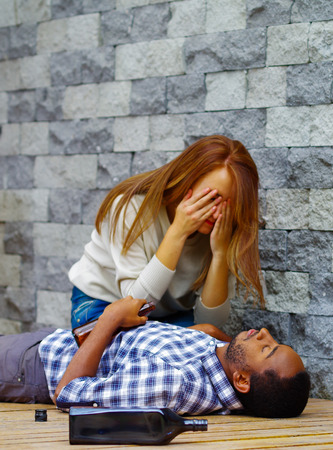 shaking out: Man wearing casual clothes lying drunk passed out on wooden surface, pretty woman sitting beside him trying to get contact by touching and shaking.