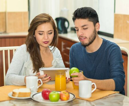hostel: Young charming couple sitting by breakfast table looking at tablet screen, fruits, juice and coffee placed in front, hostel environment.