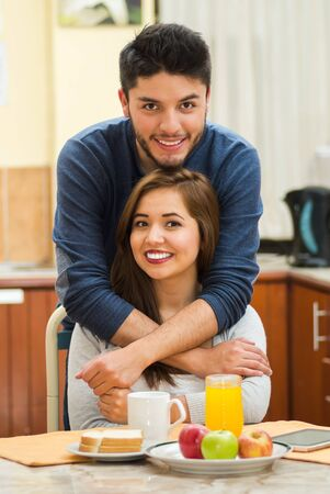 hostel: Young charming couple embracing while posing next to breakfast table, man standing behind woman seated, smiling into camera, hostel guest concept. Stock Photo