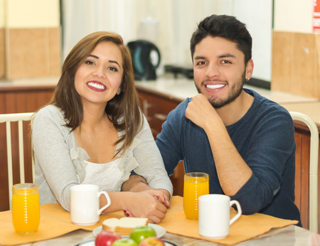 hostel: Young charming couple seated by breakfast table smiling to camera, fruits, juice and coffee placed in front, hostel environment.