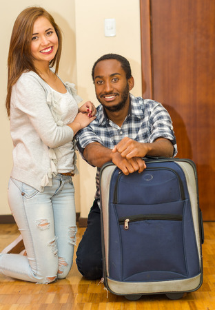 guest house: Charming young couple wearing casual clothes sitting down posing for camera smiling, blue suitcase standing on floor, hostel guest concept. Stock Photo