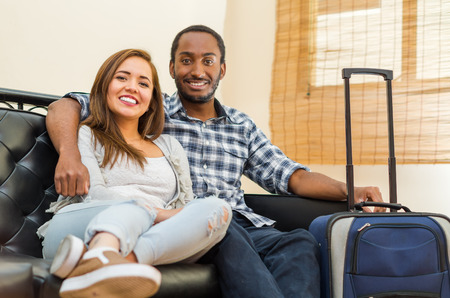 Charming young couple wearing casual clothes sitting down embracing and posing for camera smiling, blue suitcase standing on floor, hostel guest concept. Stock Photo