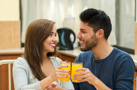 hostel: Young charming couple seated by breakfast table smiling to camera cheering with glasses, fruits, juice and coffee placed in front, hostel environment.