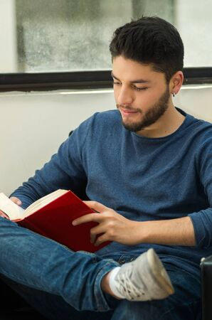 guest: Young handsome man wearing casual clothes sitting down relaxed while reading a book, hostel guest concept.