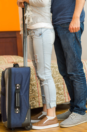 guest house: Closeup legs of couple wearing jeans, standing next to bed, blue suitcase on floor, hostel concept.
