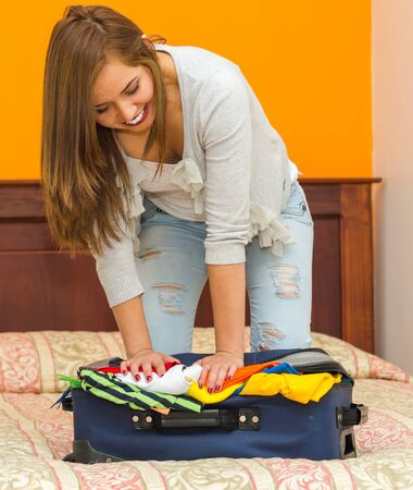 guest house: Pretty young hispanic woman using her bodyweight pushing clothes into suitcase, hostel guest concept.