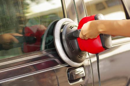 hands holding a power buffer machine cleaning a car.