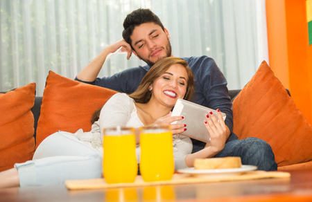 Young charming couple seated and embracing watching tablet screen in orange sofa smiling to camera, hostel environment. Stock Photo