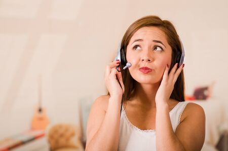 facing on camera: Young woman wearing white top and headset facing camera while interacting smiling, stressed concept. Stock Photo