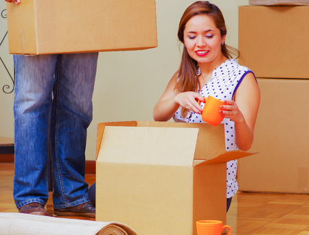 cardboard only: Charming interracial couple working together, woman sitting down unpacking cardboard box while smiling, man standing behind with only legs visible, moving in concept.