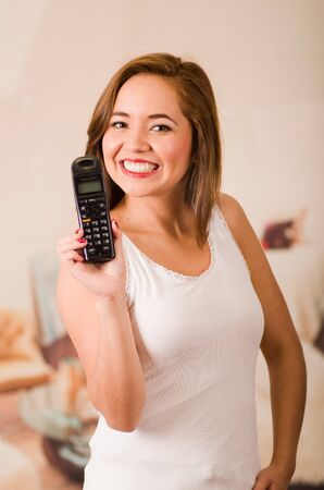 facing on camera: Young attractive woman wearing white top facing camera while holding up phone smiling.