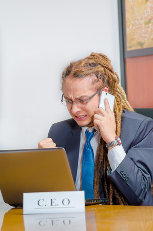 rastafari: Handsome man with dreads and business suit sitting by desk talking on mobile phone, young manager concept. Stock Photo
