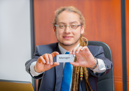 Handsome man with dreads, glasses and business suit sitting by desk holding up a paper which has the word manager written on it in his pocket, young executive concept.