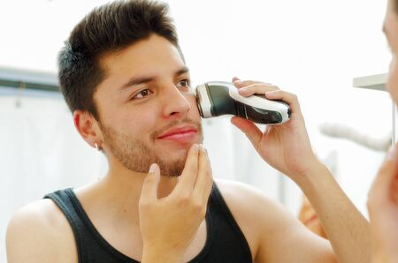 morning routine: Handsome young man wearing black singlet top looking in mirror, using electric shaving machine during morning routine concept, sligthly smiling.