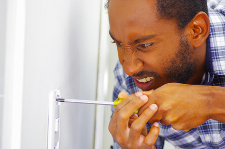 wall socket: Man wearing white and blue shirt working on electrical wall socket using screwdriver, electrician concept.