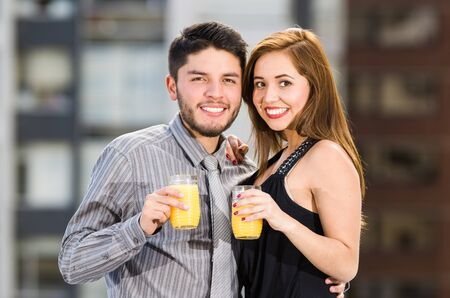 yellow to drink: Young attractive couple wearing formal clothes standing on rooftop holding glass with yellow drink, posing, smiling and embracing, city buildings background.