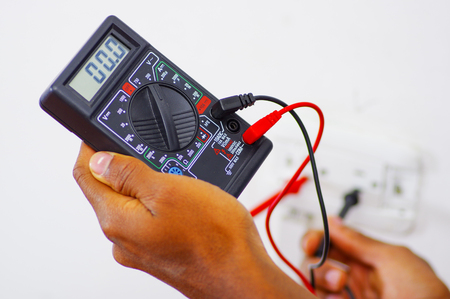 Closeup hands holding multimeter with wires connected and numbers showing on display. Stock Photo