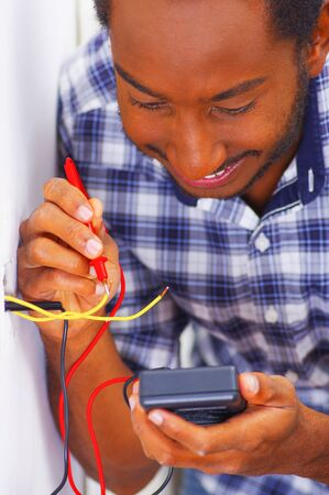 wall socket: Man wearing white and blue shirt working on electrical wall socket wires using multimeter, electrician concept. Stock Photo