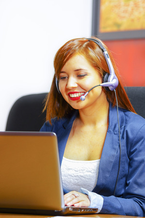 Young attractive woman wearing office clothes and headset sitting by desk looking at computer screen, working with positive facial expression. Stock Photo