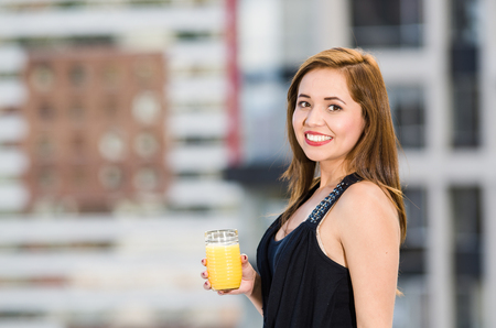 yellow to drink: Young attractive woman wearing black dress standing on rooftop, holding glass with yellow drink, smiling to camera, city buildings background. Stock Photo