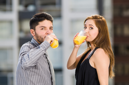 yellow to drink: Young attractive couple wearing formal clothes standing on rooftop drinking from glass with yellow drink, posing for camera, city buildings background. Stock Photo