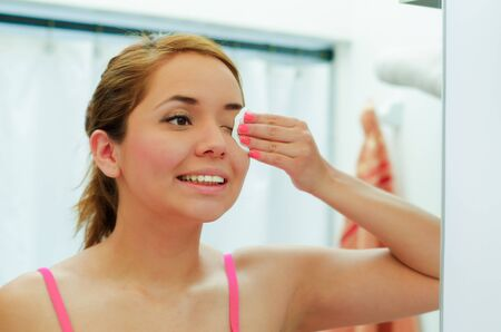 girl  care: Attractive young woman wearing pink top and white headband, using cotton patch to clean around eye, looking in mirror smiling. Stock Photo