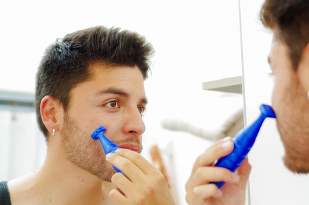 morning routine: Handsome young man wearing black singlet top looking in mirror, using shaving device during morning routine concept.