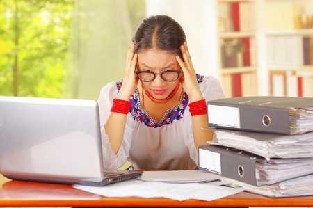 Young pretty girl wearing traditional andean clothing and glasses, sitting working by office desk with laptop computer, staring at papers touching head using hands, ring binders stacked on table, garden window background.